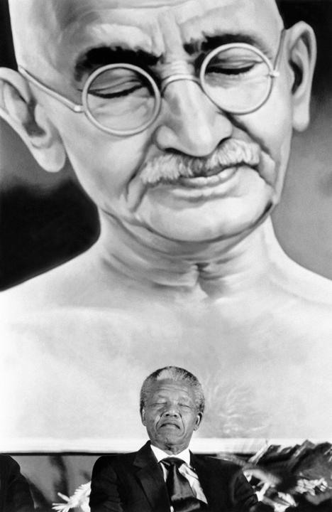 Neslon Mandela en pleine réflexion sous un portrait du Mahatma Gandhi à New Delhi, le 15 octobre 1990. AFP