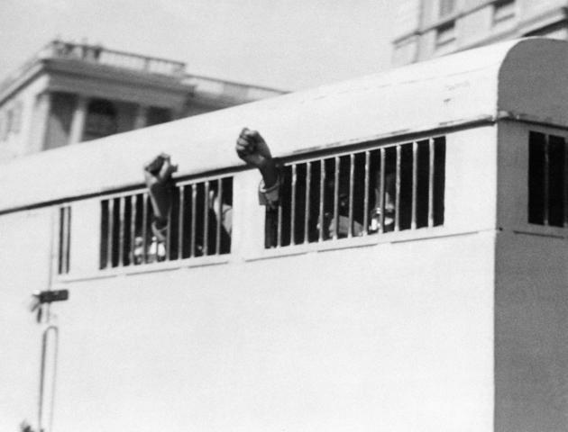 Huit membres de l'ANC (Congrès national africain), dont Nelson Mandela, condamnés à la prison à perpétuité pour complot et trahison, quittent le Palais de justice de Pretoria les poings levés, le 16 juin 1964. AFP